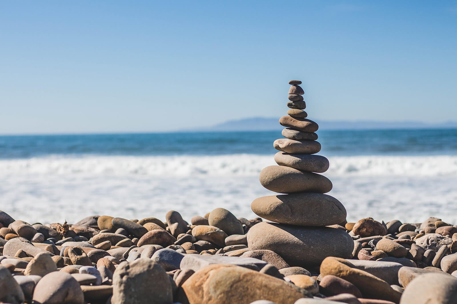 rocks stacked on top of each other along a beach
