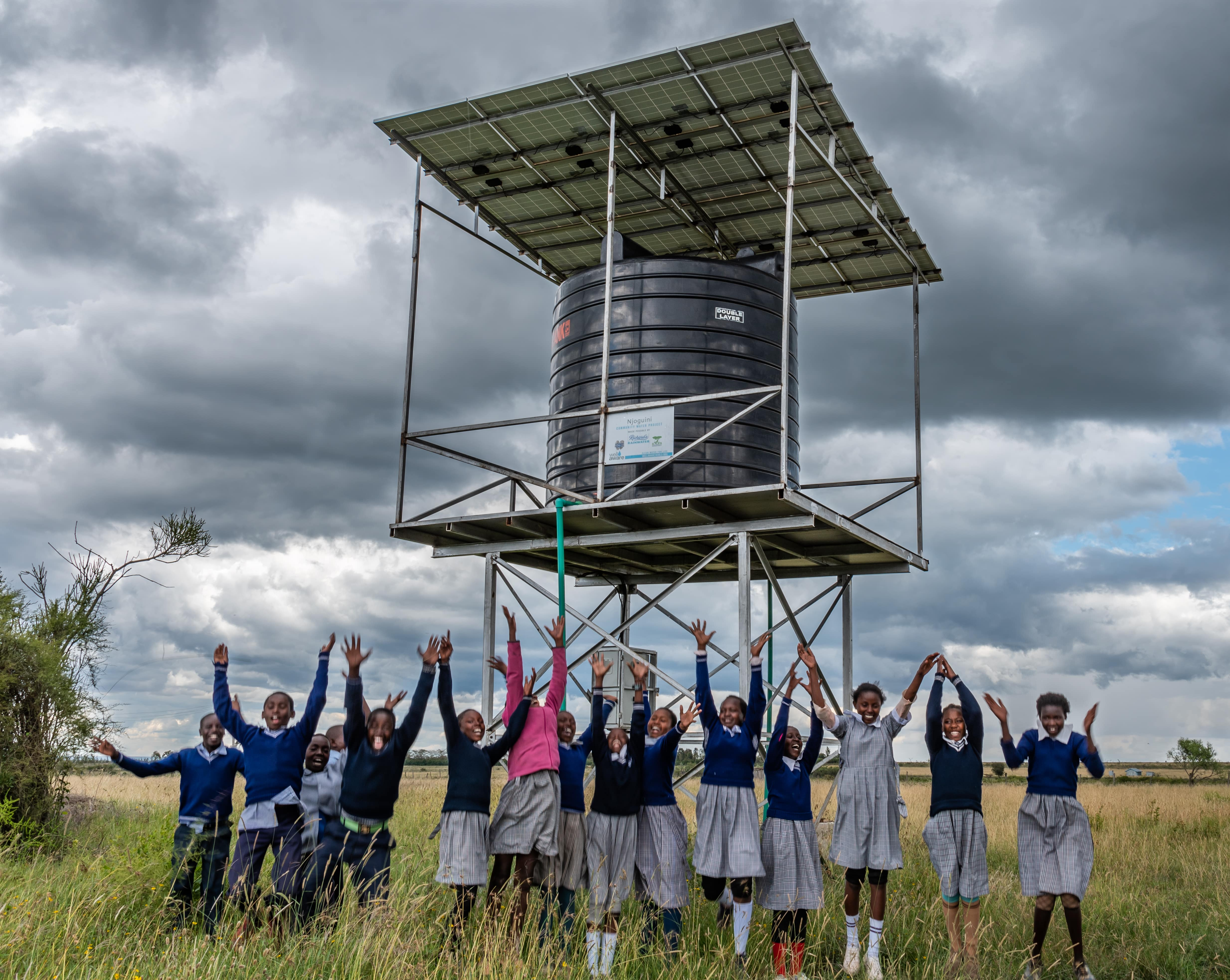 Njoguini students jumping in front of a Well Aware water tank